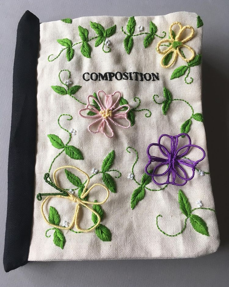 front cover of a hand-sewn off-white canvas fabric composition book decorated with yellow, pink, and purple hand-embroidered flowers, leaves, and butterflies