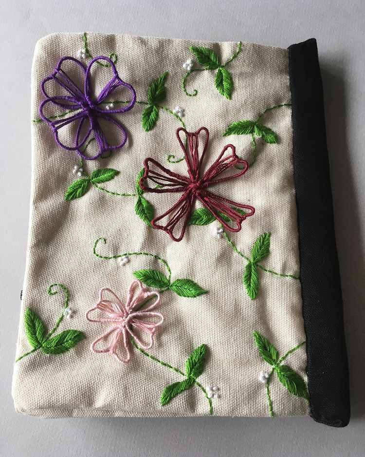 back cover of a hand-sewn off-white canvas fabric composition book decorated with yellow, pink, and purple hand-embroidered flowers, leaves, and butterflies