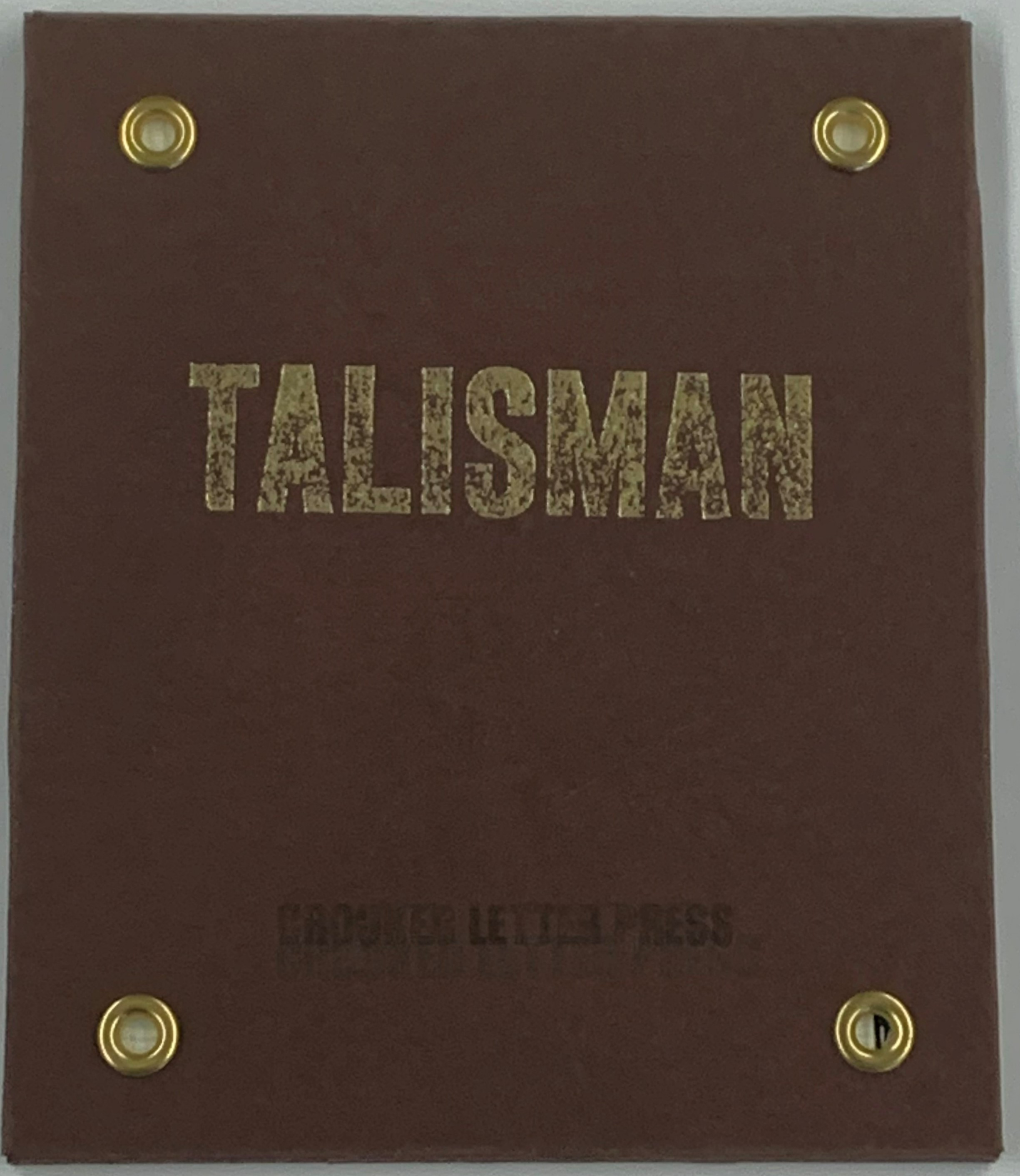 """brown cover of a wrapped enclosure with gold grommets at each corner, """"Talisman"""" printed in gold and all caps in the middle, and """"Crooked Letter Press"""" printed in black and all caps at the bottom"""